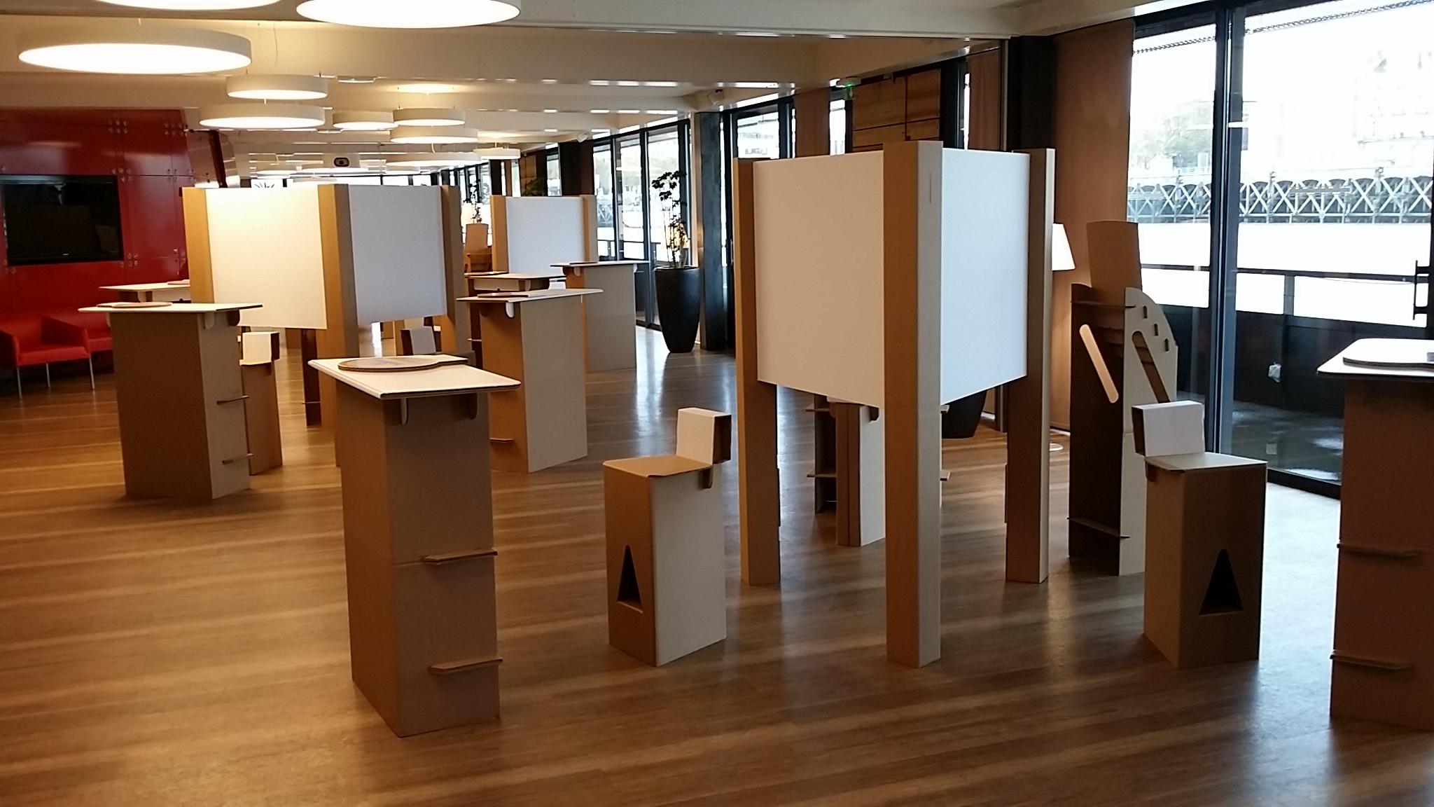 Stand en Carton composé d'un taboulet haut avec dossier, d'une banque d'accueil en carton et d'un fond de stand